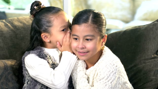 two hispanic sisters whispering secrets to each other - whispering stock videos & royalty-free footage