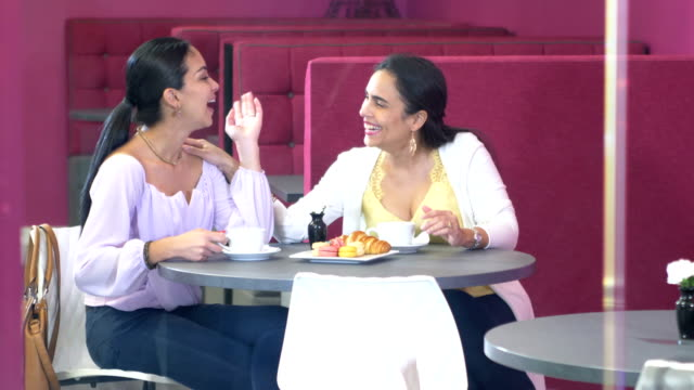 two hispanic woman chatting over coffee, pastries - sitting stock videos & royalty-free footage
