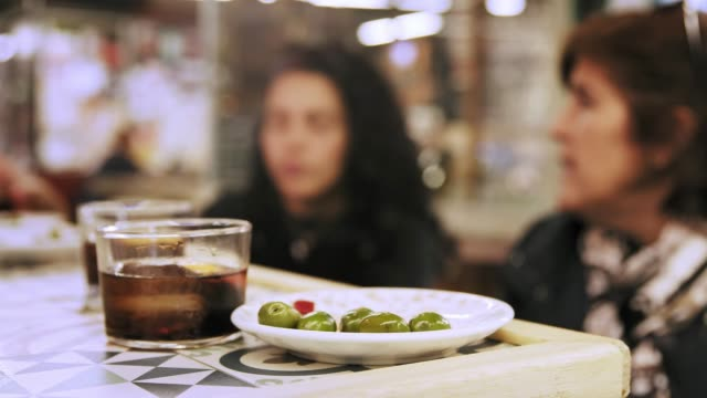 two hispanic women having a drink and tapas snack in public market - tapas stock videos & royalty-free footage