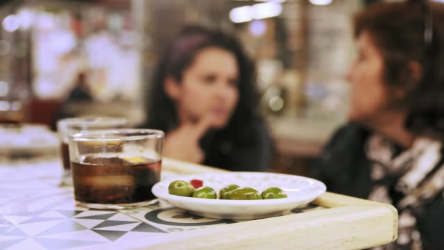 two hispanic women having a drink and tapas snack in public market - appetizer stock videos & royalty-free footage