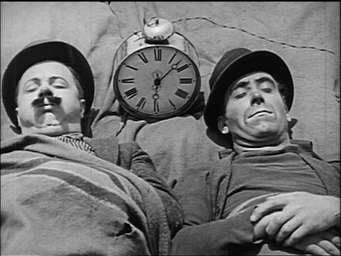 b/w 1920 two hobos (billy bevan + andy clyde) sleeping on ground next to large alarm clock - wasting time stock videos & royalty-free footage