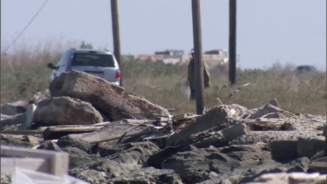 two homeowners approach the rubble from a home in a hurricane's aftermath. - rubble stock-videos und b-roll-filmmaterial