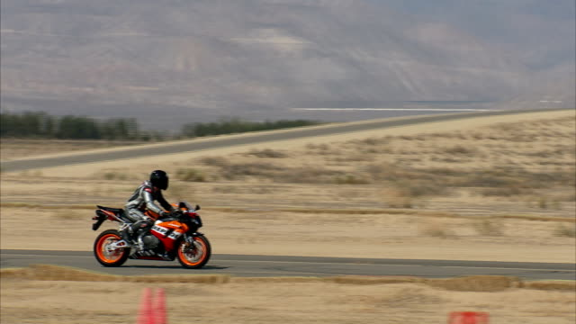 two honda riders accelerate on a desert test track. - honda stock videos & royalty-free footage