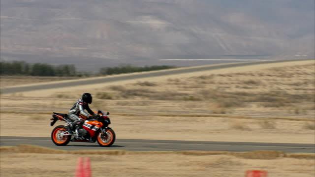 two honda riders accelerate on a desert test track. - honda bildbanksvideor och videomaterial från bakom kulisserna