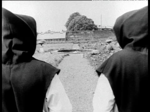 two hooded cistercian monks walk up pathway portglenone county antrim; 18 aug 67 - cappuccio video stock e b–roll