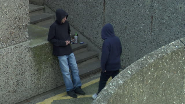 ha ws two hooded youths looking shifty and exchanging wrapped package / london, england - criminal stock videos & royalty-free footage