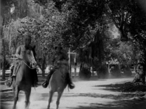 two horseback riders male female dressed in western clothing cowboy hats galloping horses down dirt road on ranch dismounting tying reins to post... - gallop animal gait stock videos & royalty-free footage