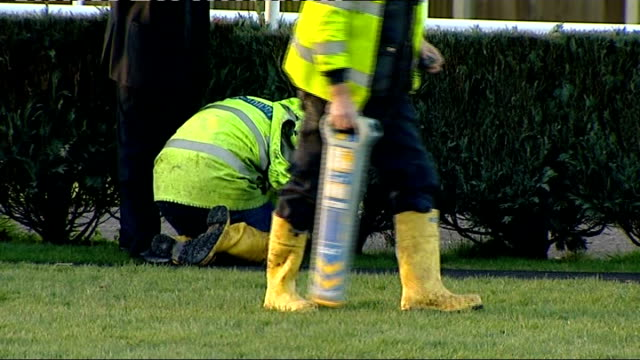 two horses die at newbury; gvs people inspecting scene of accident one with a detecting machine / wide shot racecourse / zoom in sign saying 'racing... - newbury inghilterra video stock e b–roll