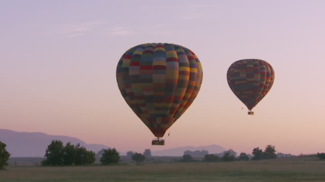 Two hot air balloons ascend above a field. Available in HD