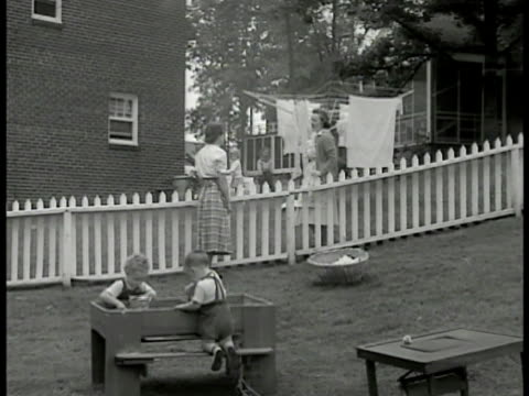 two housewives talking over fence children playing fg laundry hanging bg ms housewives talking cu woman talking virginia americana suburbia - fence stock videos & royalty-free footage