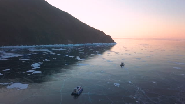 two hovercraft ride on the ice of lake baikal at dawn. lake baikal in winter. aerial view - hovercraft stock videos & royalty-free footage