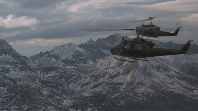 AIR TO AIR, Two Huey helicopters flying over Rocky Mountains, Colorado, USA