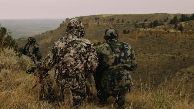 two hunters sit, silhouetted against the rugged mountain terrain they are hunting. their camouflage makes they almost disappear into the surroundings. - camouflage stock videos & royalty-free footage