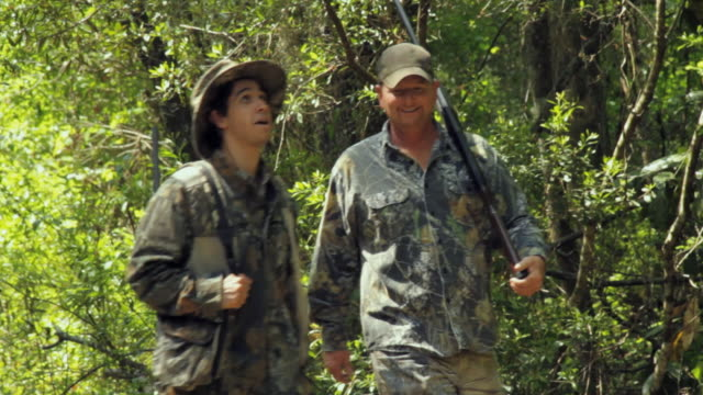 vidéos et rushes de ms two hunters with rifles walking and talking through forest / madison, florida, usa - tenue de camouflage