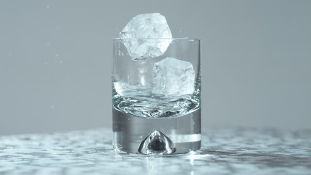 two ice cubes dropping in whiskey glass / slow motion