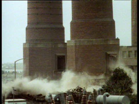 Two identical chimney stack towers being blown up for the purpose of demolition