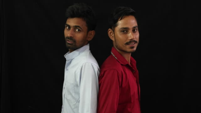 two indian friends talking to each with their backs to each other and pointing towards the camera - stoppelbart stock-videos und b-roll-filmmaterial
