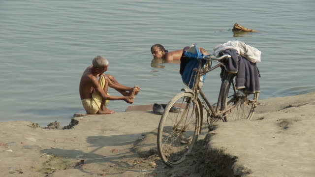 two indian men bathe in the ganges near a bicycle. - taking a bath stock videos & royalty-free footage