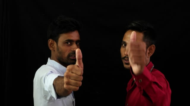 two indian men face to face talking and then giving a thumbs up towards the camera - stoppelbart stock-videos und b-roll-filmmaterial