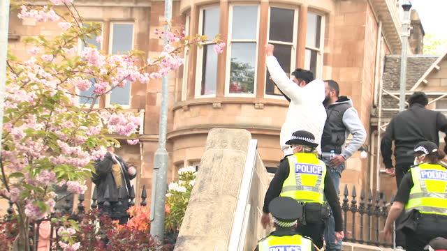 two indian nationals wave protesters in glasgow who helped with their release after they were detained in a home office van by immigration officers - politics concept stock videos & royalty-free footage