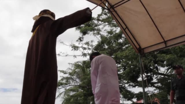 two indonesian men are caned in front of a jeering crowd as a punishment for gay sex in a first for the muslim majority country where there is... - caning stock videos and b-roll footage