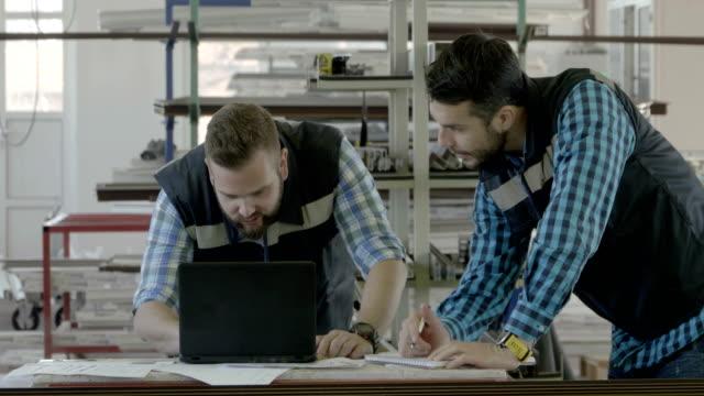 stockvideo's en b-roll-footage met twee industrieel ingenieurs met laptop - productielijn werker
