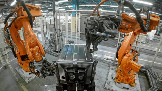 TIME LAPSE Two industrial robots welding metal frames