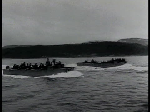 two invasion barges w/ soldiers on water landing on muddy shore. soldiers out of barges running on shore houses bg. wwii - narrating stock videos & royalty-free footage
