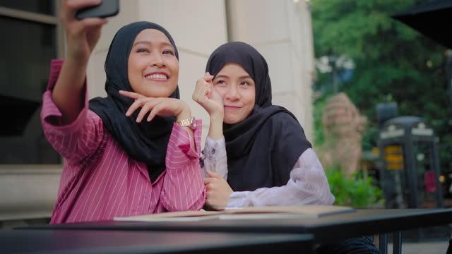 vidéos et rushes de deux islamique prenant une photo sur le téléphone intelligent tout en voyageant. - vêtement religieux