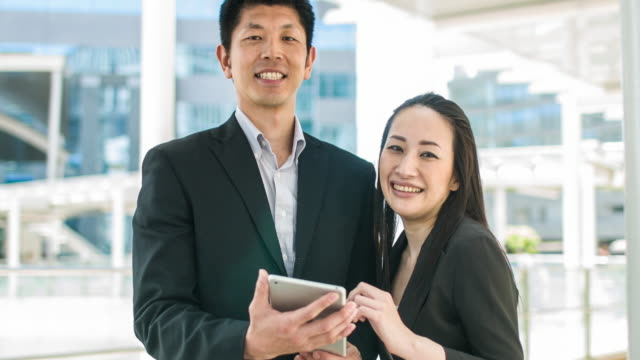 Two Japanese business people working with digital tablet