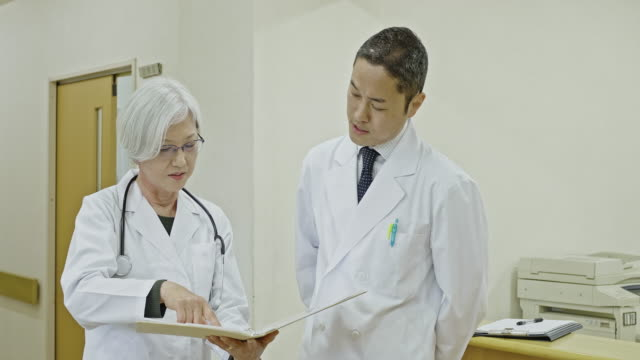 two japanese doctors discussing medical patient record at hospital - eyeglasses stock videos & royalty-free footage