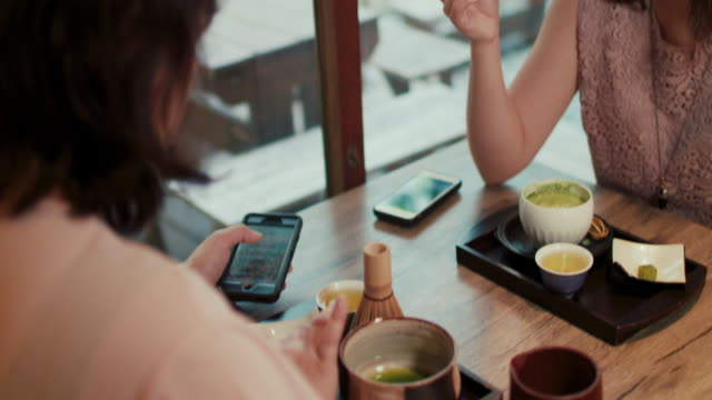 Two japanese women eating, looking at smart phone at a restaurant in Tokyo, Japan