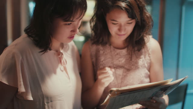 two japanese women looking at menu at a restaurant in tokyo, japan - asian colleague stock videos & royalty-free footage