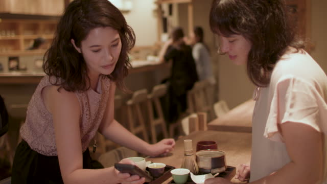 two japanese women looking at smart phone at a restaurant in tokyo, japan - 温かい飲み物点の映像素材/bロール