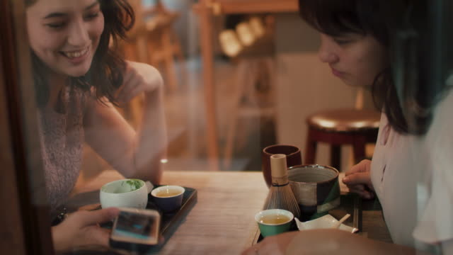 two japanese women looking at smart phone, laughing at a restaurant in tokyo, japan - 昼食点の映像素材/bロール