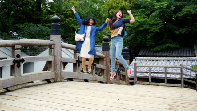 Two Japanese Women Tourists Jumping For Joy