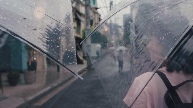 two japanese women walking in the rain with umbrellas in tokyo, japan - 雨粒点の映像素材/bロール