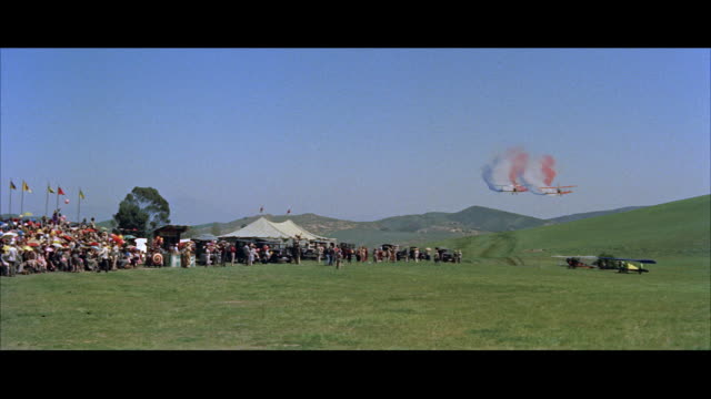 ws two jenny biplane airplanes flying from background and trailing colored smoke during air show - anno 1957 video stock e b–roll