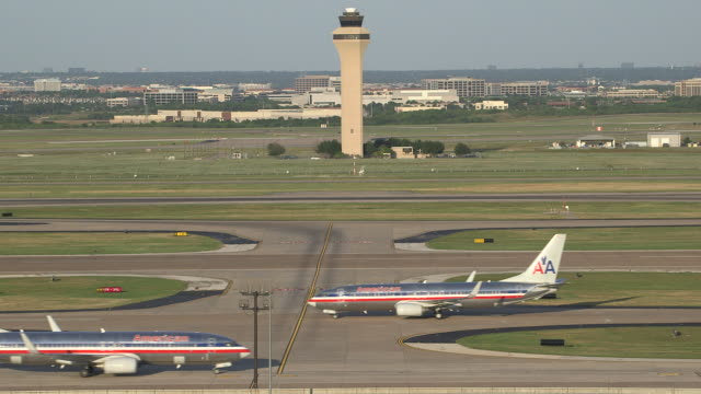Two jet passenger aircraft (Boeing 737-800) cross during taxi with control tower in background/DFW International Airport, Dallas-Fort Worth, Texas, USA