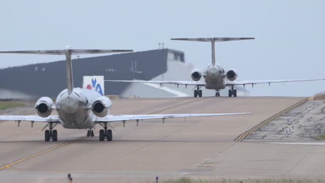 Two jet passenger planes (MD-80) taxi between runways - telephoto perspective/DFW International Airport, Dallas-Fort Worth, Texas, USA
