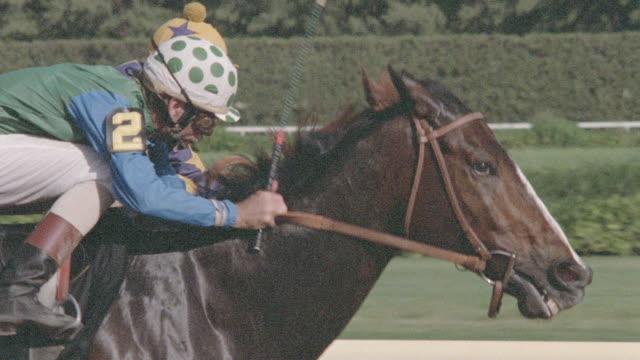 two jockeys vie for position in a horse race. - 競走馬点の映像素材/bロール