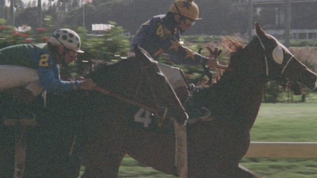 two jockeys vie for position in a horse race. - horse racing stock videos & royalty-free footage