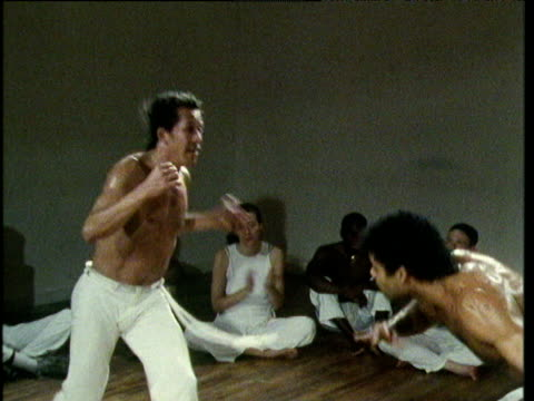 Two jogardors wearing traditional white trousers perform repertoire of high speed front and back spinning kicks during capoeira jogo watched by circle of capoeiristas New York 1980's
