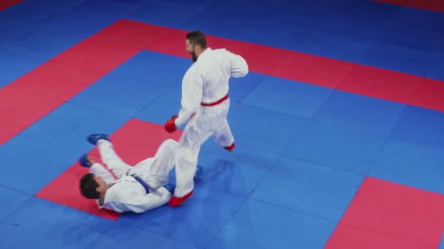 vídeos de stock, filmes e b-roll de luta de dois karaté no tatami na competição - karate