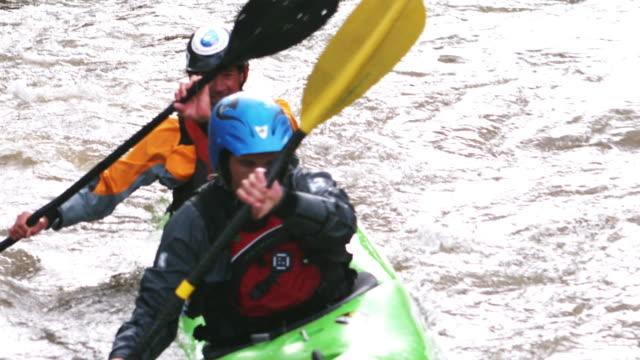 slo mo ms ha pan two kayakers in dual seat whitewater kayak paddling through river rapids, glenwood springs, colorado, usa - helmet stock videos & royalty-free footage