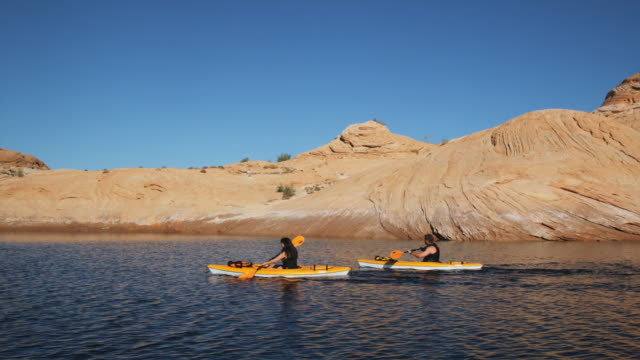 two kayakers on a desert lake
