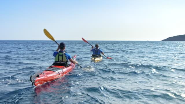 zwei kajakfahrer paddeln ihre see-kajaks im sonnenschein - ruderboot stock-videos und b-roll-filmmaterial