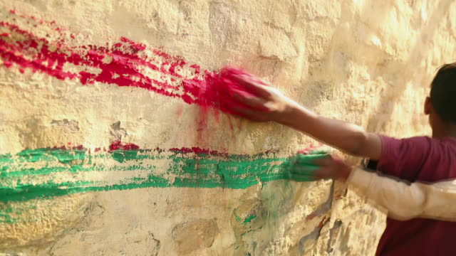 two kids applying red and green color on the wall, ballabhgarh, haryana, india - haryana stock-videos und b-roll-filmmaterial