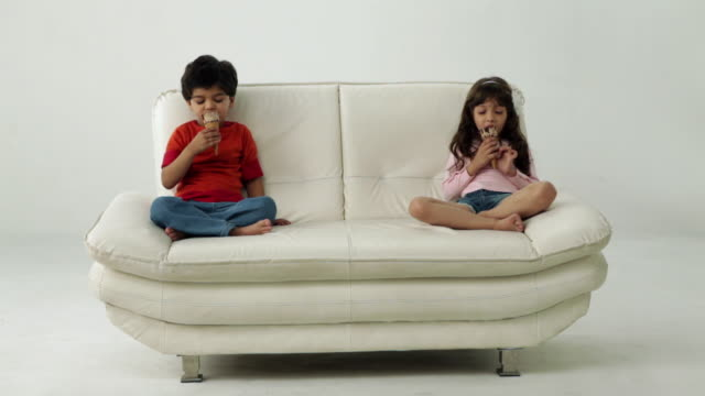 Two kids eating an ice cream on the couch