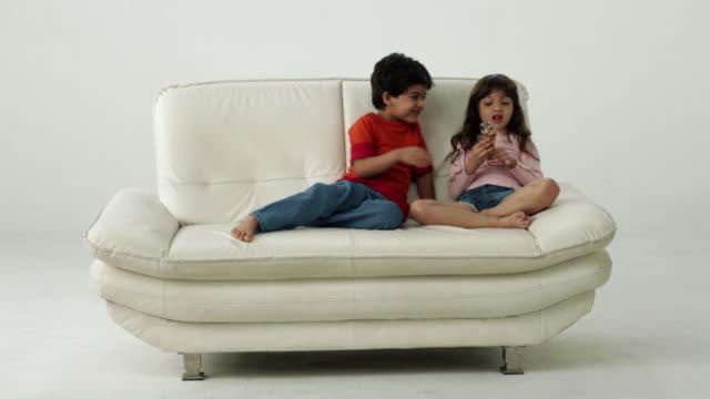 two kids eating an ice cream on the couch  - 分かち合い点の映像素材/bロール